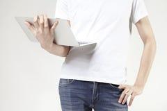 Equipaggi la maglietta d'uso con il computer portatile moderno in mani del ` s dell'uomo, maglietta bianca d'uso del tipo, lavora Fotografia Stock