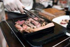 Equipaggi la mano ad un barbecue con carne e pepe Immagini Stock Libere da Diritti