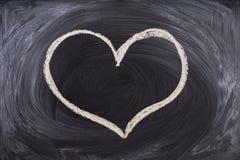 Equipaggi la mano che disegna un cuore con gesso in una lavagna fotografia stock