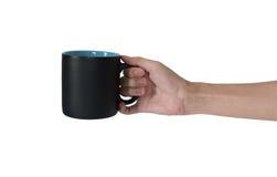 Equipaggi la mano che giudica una tazza nera isolata su fondo bianco immagine stock