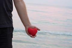 Equipaggi la mano che tiene il cuore rosso sulla spiaggia fotografie stock libere da diritti