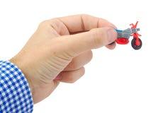 Equipaggi la mano che tiene un giocattolo di plastica della bicicletta su bianco Immagine Stock