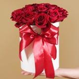 Equipaggi la mano che tiene un mazzo ricco del regalo di 21 rosa rossa composizione Immagini Stock