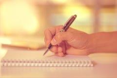 Equipaggi la mano che tiene una scrittura della penna sul taccuino Immagini Stock