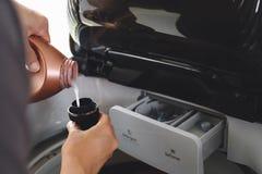 Equipaggi la mano che versa il detersivo e l'emolliente di lavanderia liquidi in bottiglia fotografie stock