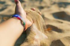 Equipaggi la mano che versa la sabbia fine sulla spiaggia al tramonto fotografia stock