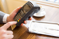 Equipaggi la mano con il colpo della carta di credito tramite il terminale da vendere, in re Fotografia Stock