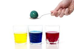 Equipaggi la mano con il cucchiaio, tintura che colora l'uovo di Pasqua Fotografia Stock Libera da Diritti