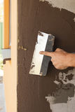 Equipaggi la mano con la cazzuola che intonaca una parete della casa Fotografie Stock Libere da Diritti