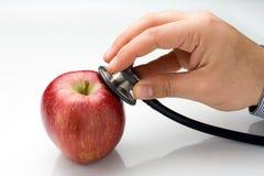 Il dottore Examining Red Apple Immagini Stock Libere da Diritti
