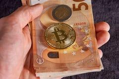 Equipaggi la mano del ` s con bitcoin e 50 cinquanta euro delle banconote delle fatture degli ambiti di provenienza Fotografia Stock