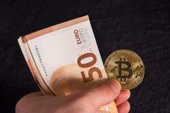 Equipaggi la mano del ` s con bitcoin e 50 cinquanta euro delle banconote delle fatture degli ambiti di provenienza Immagine Stock Libera da Diritti