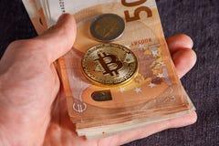 Equipaggi la mano del ` s con bitcoin e 50 cinquanta euro delle banconote delle fatture degli ambiti di provenienza Immagini Stock Libere da Diritti