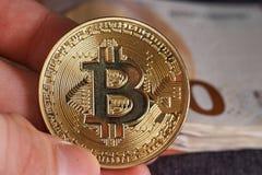 Equipaggi la mano del ` s con bitcoin e 50 cinquanta euro delle banconote delle fatture degli ambiti di provenienza Macro Fotografie Stock