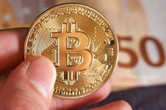 Equipaggi la mano del ` s con bitcoin e 50 cinquanta euro delle banconote delle fatture degli ambiti di provenienza macro Immagine Stock