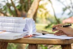 Equipaggi la mano del ` s con scrittura della penna sul taccuino in parco fotografia stock