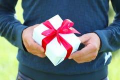 Equipaggi la mano del ` s con un piccolo contenitore di regalo bianco con l'arco Fotografia Stock