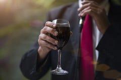 Equipaggi la mano del ` s con un vetro di vino rosso Fotografie Stock Libere da Diritti