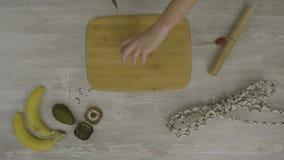 Equipaggi la mano del ` s sul bordo di legno con un coltello che taglia una salsiccia Sulla tavola sono molte forbici, un coltell stock footage