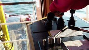 Equipaggi la mano del ` s in una leva di comando rossa dell'argano del vestito sul ponte della nave Vista del primo piano video d archivio