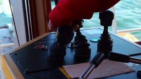 Equipaggi la mano del ` s in una leva di comando rossa dell'argano del vestito sul ponte della nave Vista del primo piano stock footage