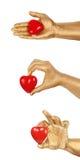 Equipaggi la mano dorata del ` s con un cuore rosso sopra bianco Fotografia Stock Libera da Diritti