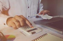 Equipaggi la mano facendo uso del calcolatore con calcolano le fatture e il dat finanziario immagini stock libere da diritti