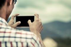 Equipaggi la mano facendo uso del cellulare, lo smartphone, telefono per prendere la foto Fotografia Stock