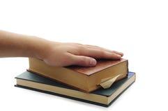 Equipaggi la mano sui libri marroni e verdi. Fotografia Stock
