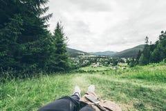 Equipaggi la menzogne sulla terra e godere della vista delle montagne Immagini Stock Libere da Diritti