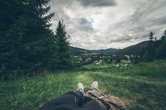 Equipaggi la menzogne sulla terra e godere della vista delle montagne Fotografia Stock Libera da Diritti