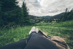 Equipaggi la menzogne sulla terra e godere della vista delle montagne Fotografie Stock Libere da Diritti
