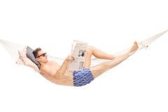 Equipaggi la menzogne in un'amaca e la lettura del giornale Immagine Stock Libera da Diritti