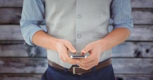 Equipaggi la metà di sezione con il telefono contro il pannello di legno blu confuso Fotografia Stock