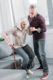 Equipaggi la moglie senior d'aiuto con il bastone da passeggio per camminare Immagine Stock Libera da Diritti