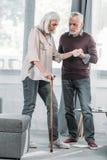 Equipaggi la moglie senior d'aiuto con il bastone da passeggio per camminare Immagine Stock