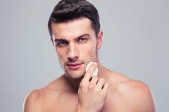 Equipaggi la pelle del fronte di pulizia con i cuscinetti di cotone dell'ovatta Immagini Stock Libere da Diritti