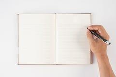 Equipaggi la penna di tenuta della mano ed il taccuino di scrittura su fondo bianco f Immagini Stock Libere da Diritti