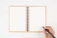 Equipaggi la penna di tenuta della mano ed il taccuino di scrittura su fondo bianco f Fotografie Stock