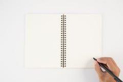 Equipaggi la penna di tenuta della mano ed il taccuino di scrittura su fondo bianco f Fotografia Stock Libera da Diritti