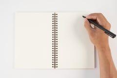 Equipaggi la penna di tenuta della mano ed il taccuino di scrittura su fondo bianco f Immagine Stock