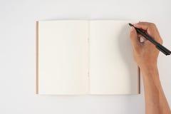 Equipaggi la penna di tenuta della mano ed il taccuino di scrittura su fondo bianco f Immagine Stock Libera da Diritti