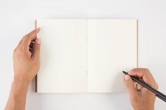 Equipaggi la penna di tenuta della mano ed il taccuino di scrittura su fondo bianco f Fotografie Stock Libere da Diritti