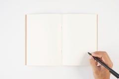Equipaggi la penna di tenuta della mano ed il taccuino di scrittura su fondo bianco f Fotografia Stock