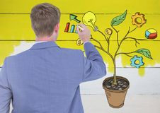 Equipaggi la penna di tenuta ed il disegno dei grafici dell'attività sui rami della pianta sulla parete Fotografie Stock Libere da Diritti