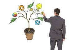 Equipaggi la penna di tenuta ed il disegno dei grafici dell'attività sui rami della pianta sulla parete Immagini Stock Libere da Diritti