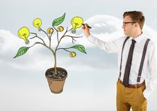 Equipaggi la penna di tenuta ed il disegno dei soldi e dei grafici di idea sui rami della pianta sulla parete Immagini Stock