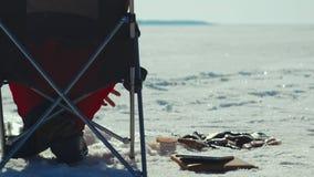 Equipaggi la pesca di pescatore sul lago dell'inverno e mettere il riuscito pesce pescato in ghiaccio archivi video