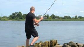 Equipaggi la pesca sotto il ponte, vista posteriore stock footage