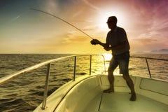 Equipaggi la pesca sul mare dalla barca immagine stock